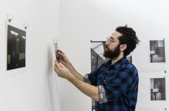 Artist Alexis Lagimodiere-Grise hangs work in his studio during the Winter BAiR 2018 residency.