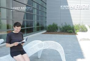 Pop-up Library visitor reading a book on a bench