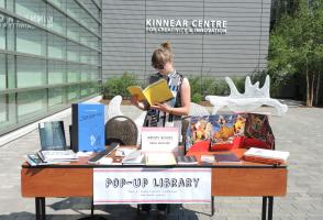 Library staff member reading a book at the pop-up library