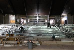 Construction crews work on the seating in a stripped down theatre.