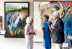 Ball attendees explore paintings that are up for auction.