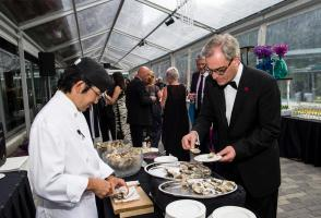 Chef serves a ball guest oysters at the champagne reception of Midsummer Ball.