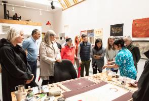Guests gather around a table as a visual artists displays her work.