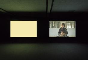 Two large screens in a dark room, one is a blank beige and the other vaguely shows a person.