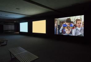 Three screens in a dark room, two are blank colours and the other shows three children.