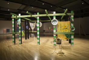 Large wood exhibit structure with green painted details and an outdoor garden semblance.