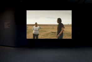 Large Screen in dark room depicting a lady in a white shirt speaking with a dark haired man.