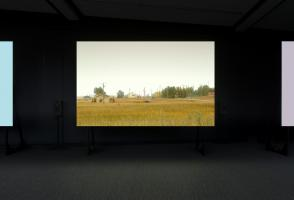 Three screens with only one centered in the frame, the centered screen depicts a flat farmland scene.