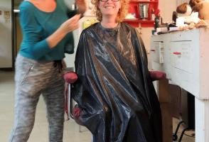 Blonde woman sits in hairdresser's chair looking very happy with her new hairdo.