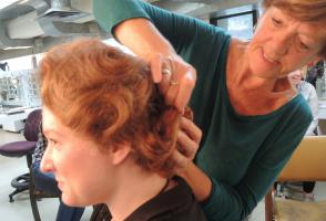 Carol Chambers pins up the back of a red wig on a woman