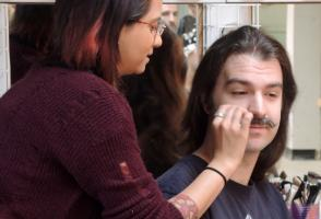 A long haired man gets a mustache applied by a woman