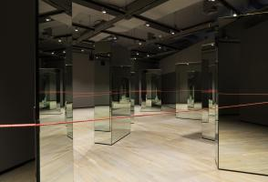 Multiple mirrors are standing in a room with a long red string connecting them all together.