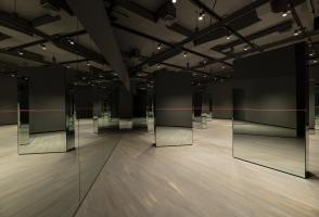 A wall of mirrors is on the left. On the right is a number of freestanding mirrors connected by a long red string.