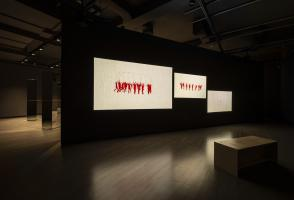 Mirrors connected by a long red string are in the background. There is a wall with three screens projected onto it. Each of the screens features red and white animations. There is one wooden bench in the foreground.