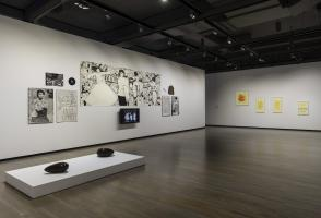 Two sculptures sit on a platform in the foreground of the image. A mixed media display is on the wall including, drawings, a record, an items of clothing and a TV screen. Five framed artworks hang on another wall in the background.