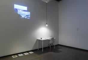 Four pieces of paper with earth are on the ground next to a white desk with a white chair. There is a binder on the desk and a single light bulb hangs above it on a black cord. Two images are projected onto the wall above the desk to the left.
