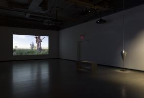 A video artwork is on the left hand side of the exhibition space and a mixed media sculpture hangs from the ceiling of the right side of the exhibition space.