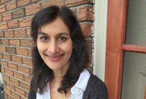 Photo of program faculty, Anita Anand, smiling into the camera, with a brick wall backdrop
