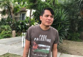 Photo of program faculty, Orlando White, outdoors, looking off-camera, wearing 'Free Palestine' t-shirt