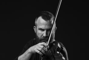 Black and white photo of man looking at camera while holding a violin
