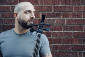 Musician Andrew Ascenzo looks to the side while posing in front of a brick wall