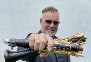 François Houle holds a deconstructed clarinet in his hand and holds it towards the camera.