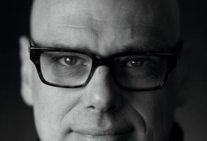 Multi-media designer, Hugh Conacher, wears glasses in a black and white photo