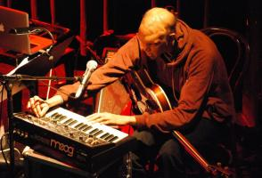 Shahzad Ismaily sits at a keyboard with a guitar in his lap. He is adjusting the keyboard and the photo is taken from above.